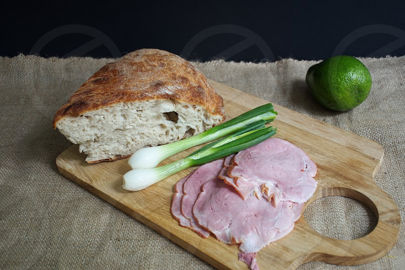 High angle view of the bread ham onion and avocado on the cutting board photo