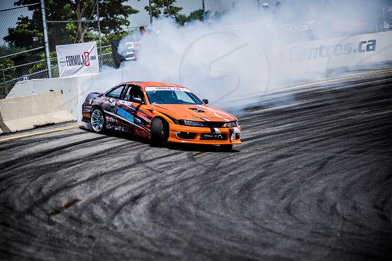 orange and b lack coupe drifting on gray concrete track during daytime photo