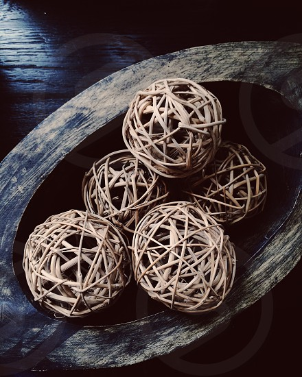 Wooden bowl with decorative round woven rattan balls on a wooden table photo