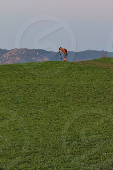 man taking a picture using a tripod in open field during daytime photo