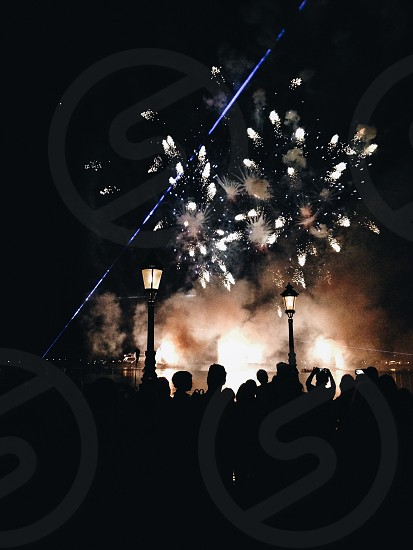 silhouette of people standing and white fireworks display beside street lamps during night time photo