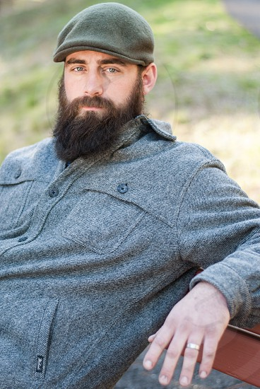 Bearded man sitting on bench in the outdoors photo