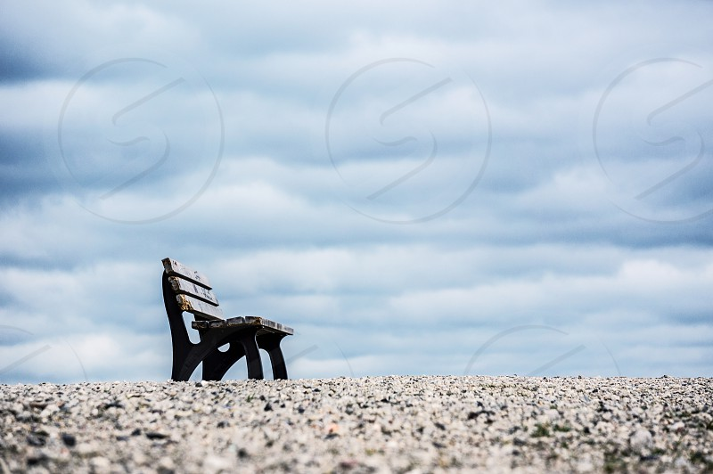 Springtime: park bench in the background blue sky and clouds photo
