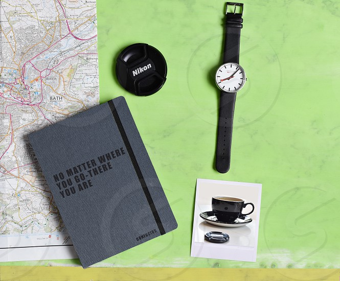 Overhead shot of a desk with notebook photograph and watch. photo