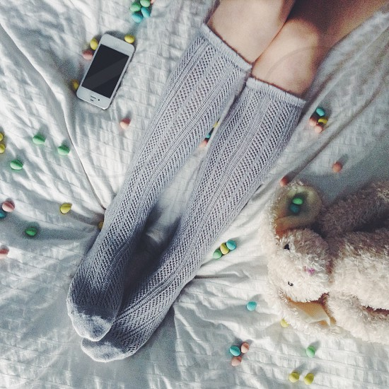 ladies gray cable knit knee socks plush bunny and white mobile device on bed photo