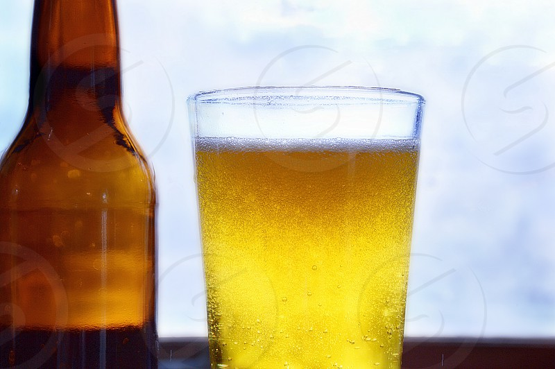 Unlabeled beer bottle with a glass of beer against bright sky photo