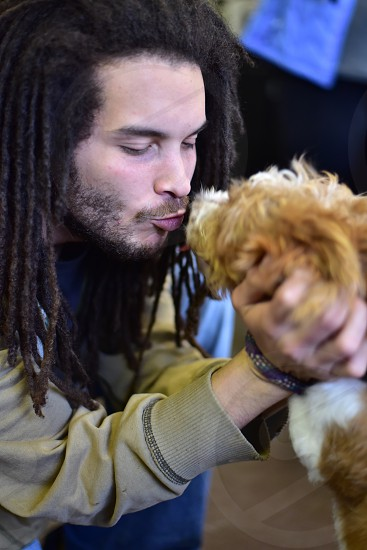 Hipster Man with Dreads & rescued puppy at shelter photo