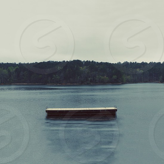 gray docked on water by green trees under gray sky photo
