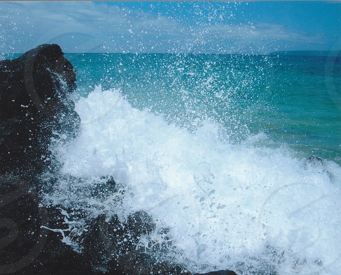 Maui Hawaii ocean wave crashes on lava rocks bubbles of white wash fly in the air  photo