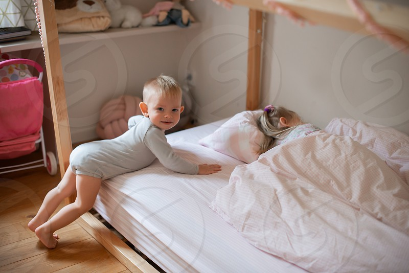 The charming children playing on the bed at home photo