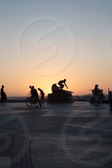 silhouette of people walking beside surfer statue during golden hour photo