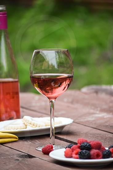 berries beside glass of wine beside white saucer photo