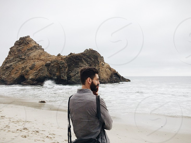 man in grey button down shirt standing on the beach on a foggy day photo