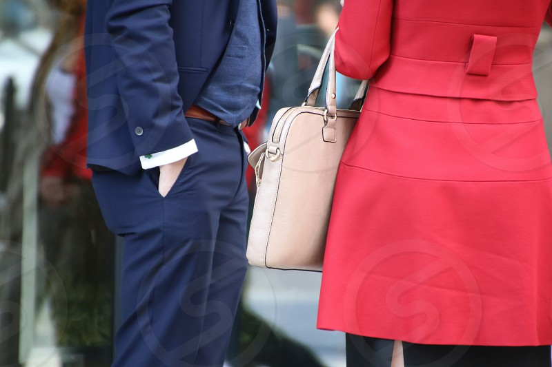 man standing with his hand in his pocket next to a woman holding a white leather bag photo