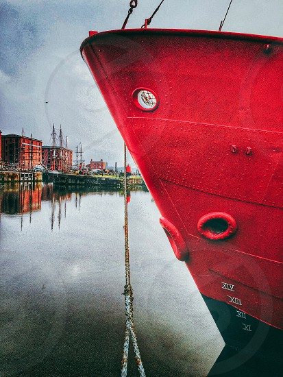 red ship on ocean near brown city buildings during daytime photo