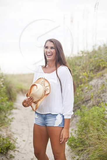 woman in white round neck peasant sleeved shirt and blue daisy dukes standing and smiling holding brown cowgirl hat photo