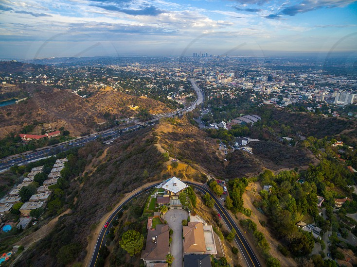 aerial photo of homes on hills and a freeway winding through the hills to a city in the distane photo