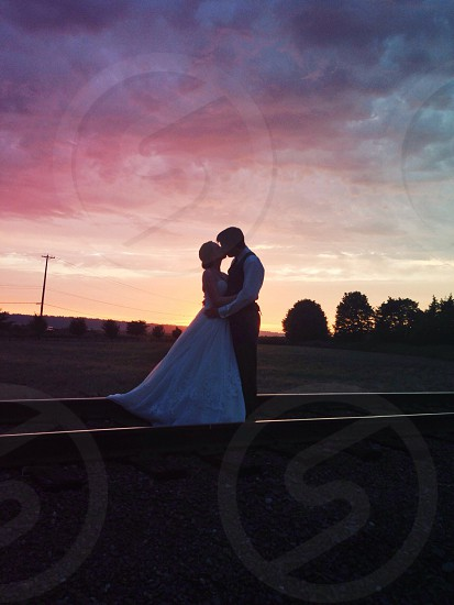 bride and groom standing on train tracks photo