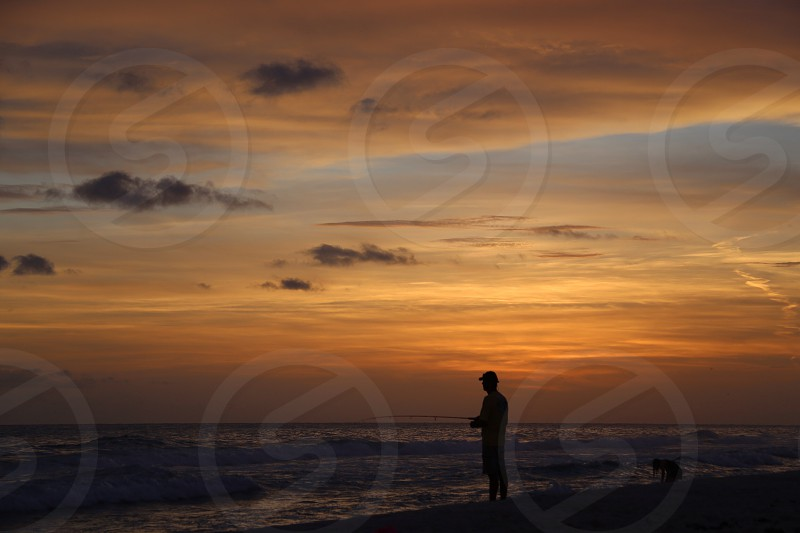 person standing seashore looking at the sea photo