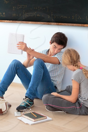 Teenagers learning by a blackboard in classroom photo