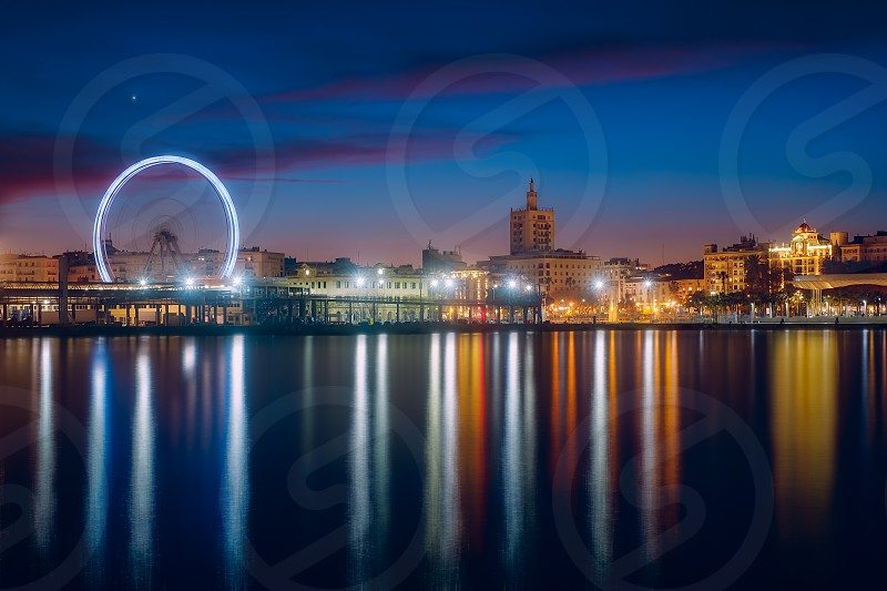 View of Malaga city and Ferris wheel from harbour Malaga Spain photo