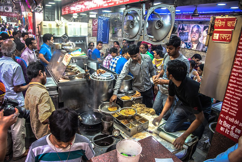 people in an area where there are foods being sold and some of them are eating and buying and the vendors are cooking the food photo