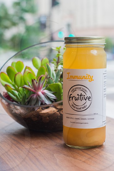 Immunity Fruitive jar beside open-globe terrarium on top of table photo