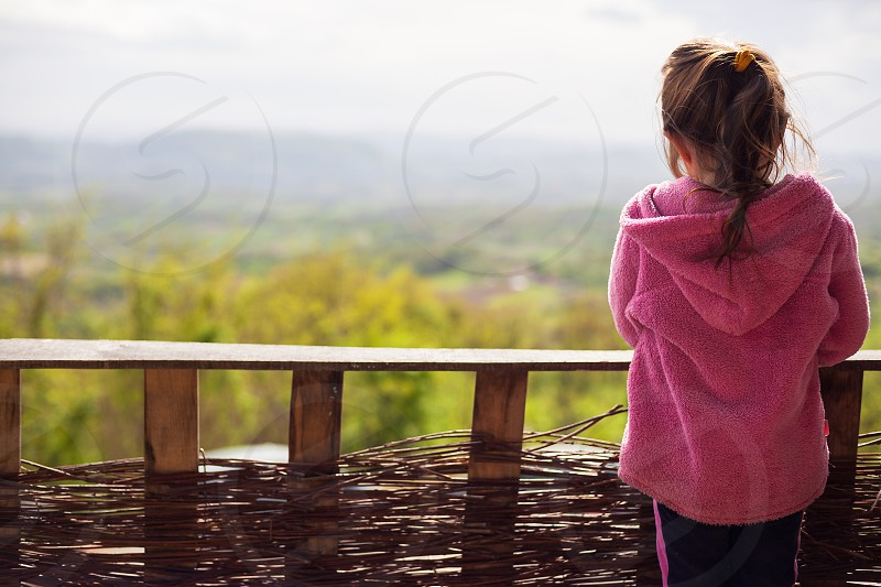 Just young girl in front of a wooden fence nature in background.  photo