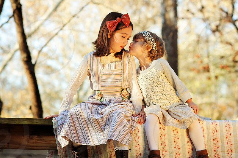two children sitting down outdoors photo