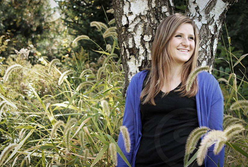 woman in black shirt and blue jacket standing in woods photo
