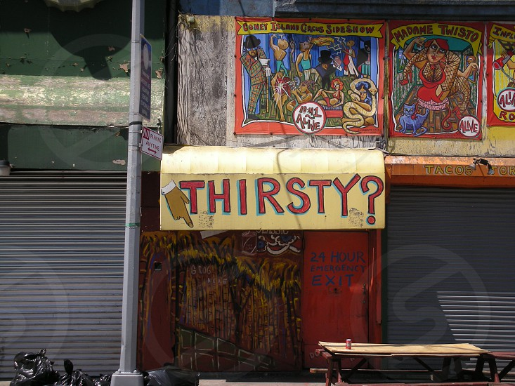 Thirsty? Sign on a building wall photo