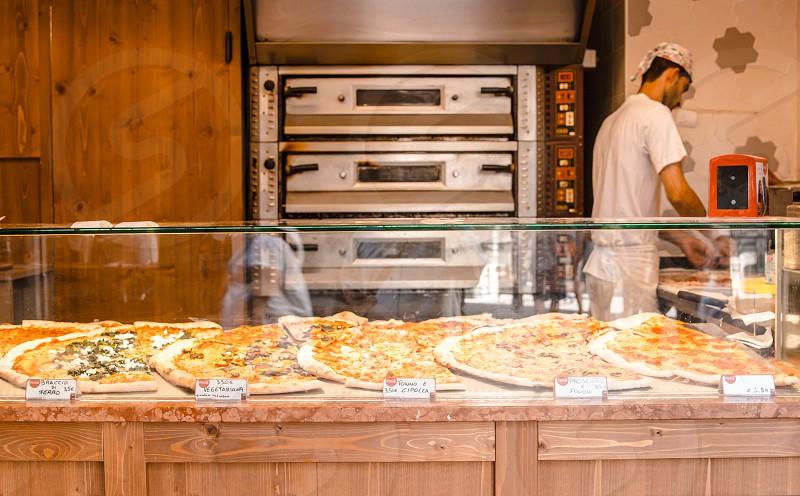 Employee Prepares Pizza At Pizzeria photo