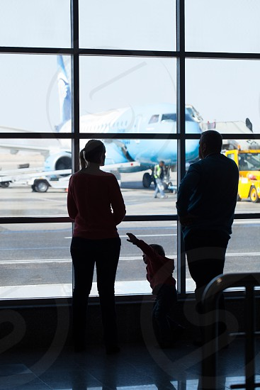 Young family watching planes at an airport standing together in front of a large glass window overlooking a jetliner being readied for takeoff photo