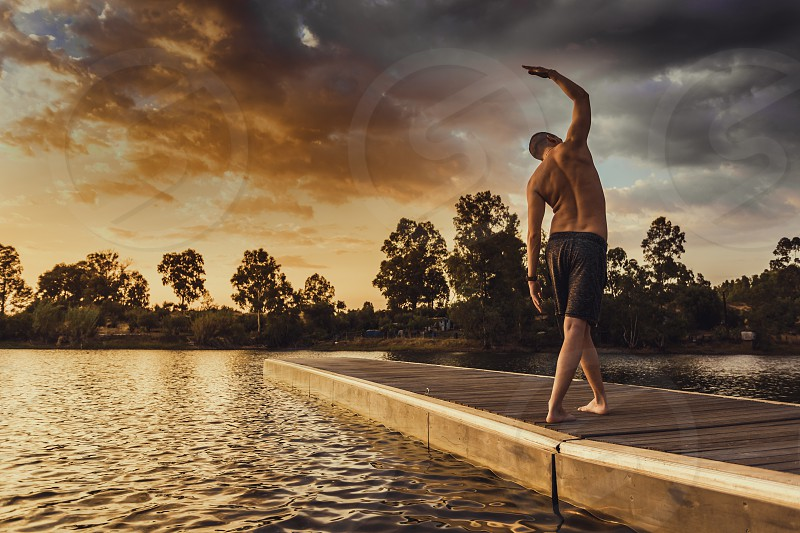 Young man doing pilates exercises standing on wooden jetty at sunset with orange sky photo