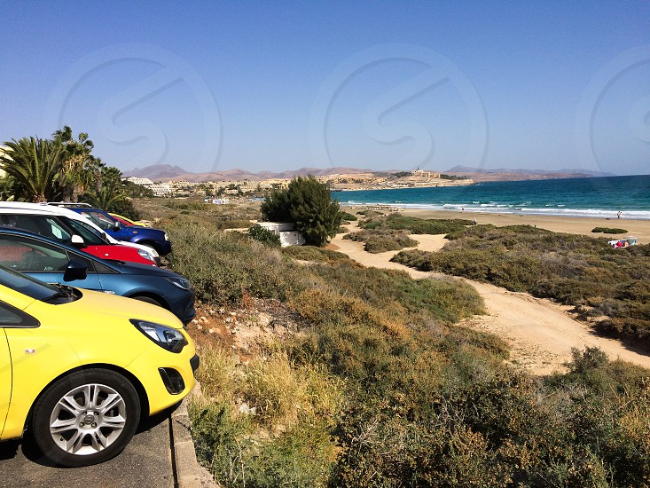 Sea ocean water beach cars travel sky island Lanzarotte Spain vacation holiday rest sun summer color yellow blue red green waves photo