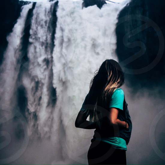 woman standing and looking at waterfalls photo