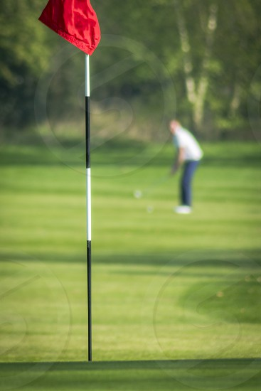 A golfer out of focus in the background prepares to play his shot towards the flag in focus in the forground. portrait orientation  photo