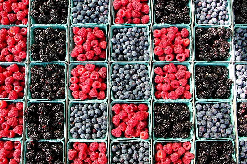 Boxes of raspberries blackberries and blueberries at a farmers market photo