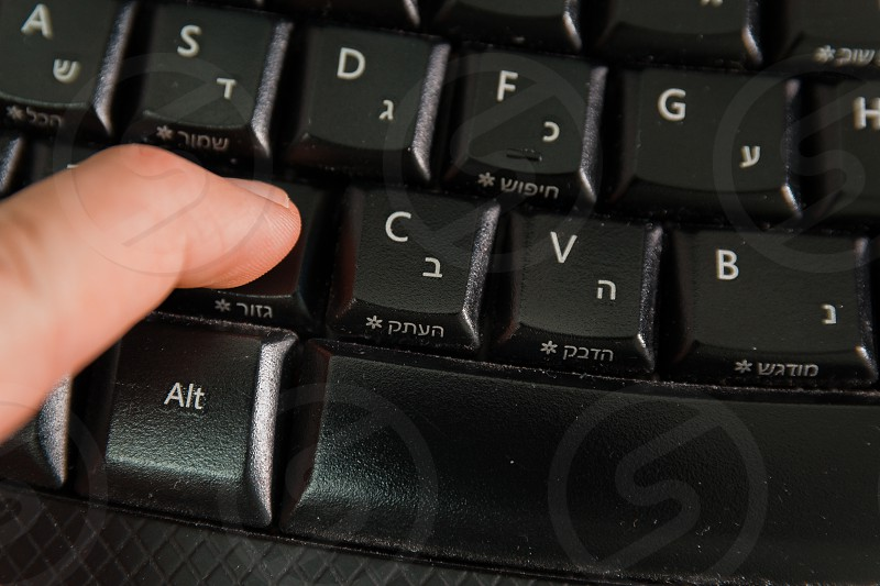 Man typing on a Wireless keyboard with letters in Hebrew and English - Press the Cut button - Top View photo