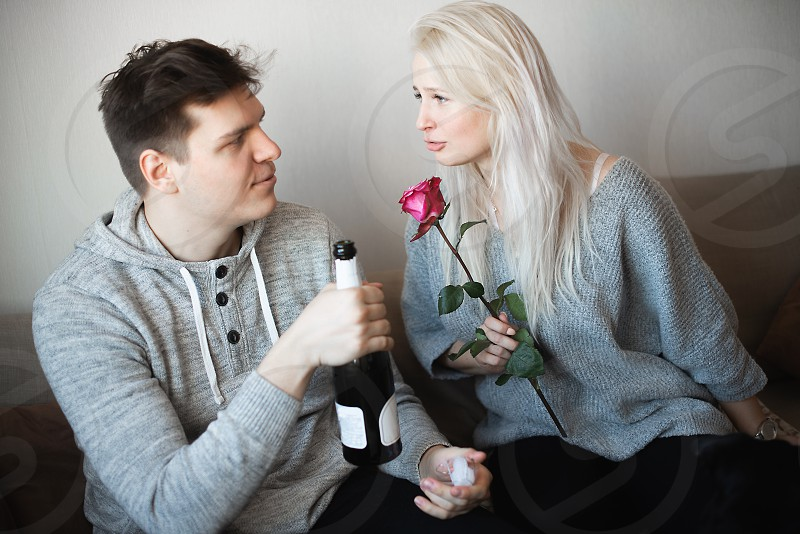 Love is a great feeling. Celebrating anniversary. Young loving couple sitting close to each other hugging and drinking white wine  photo