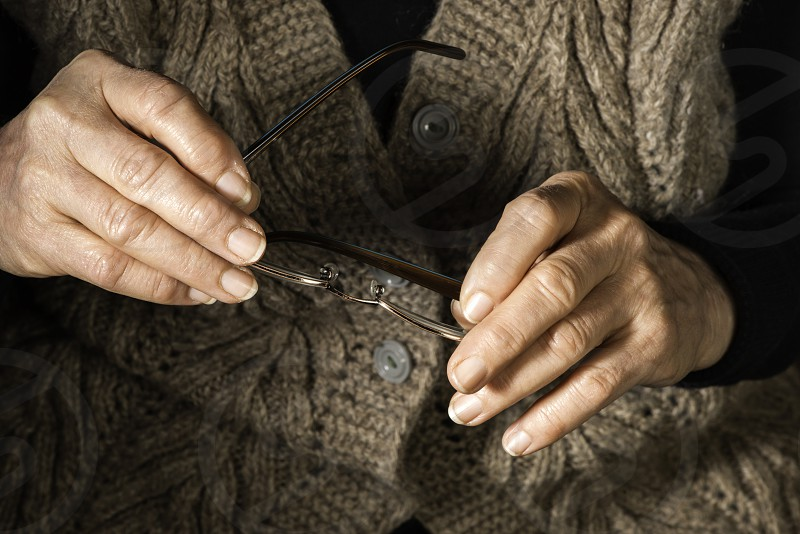Old women hands hold glasses photo