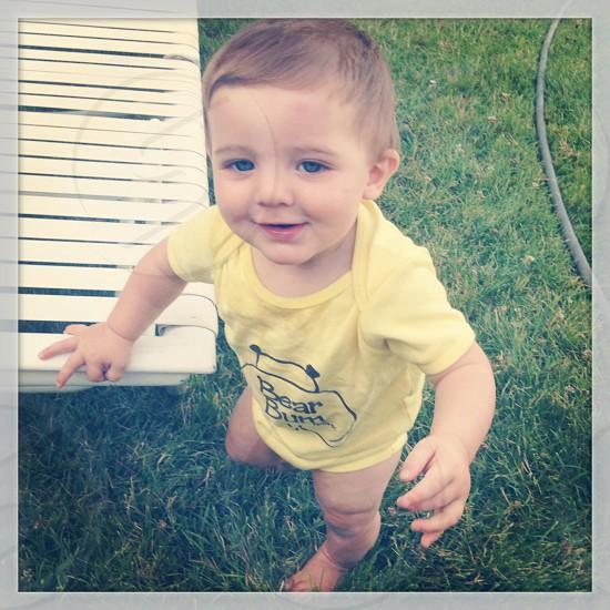 boy wearing a yellow t shirt standing photo