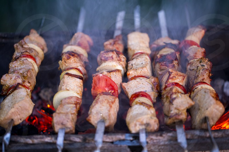 Grilled pork shish kebabs with tomatoes grilled on skewers on the grill. photo