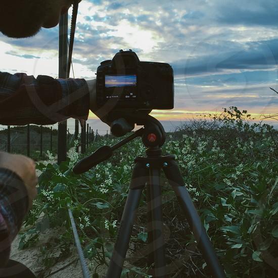 man in black sweater holding camera on tripod photo