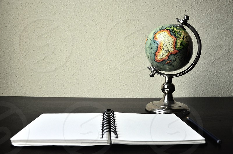 orange blue and green globe and white spiral notebook on black table photo
