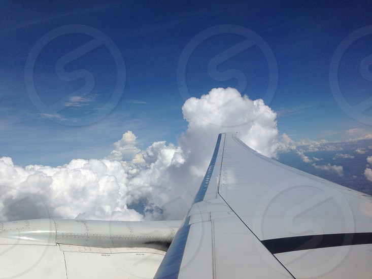 grey airplane wing with white clouds photo
