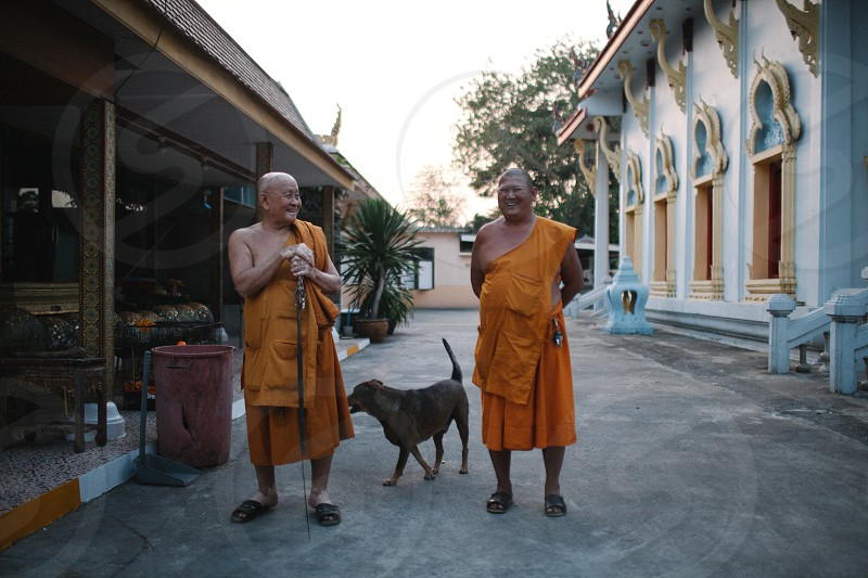 2 monks standing beside black dog and concrete building during daytime photo