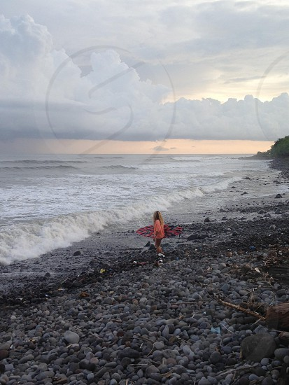 man in orange t shirt holding pink and black surfboard on sea side under cloudy sky photo
