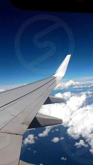 white airplane wing with turbine and white cumulus clouds outside plane window photo