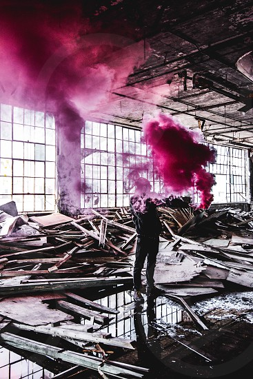 man standing in front of piled wood plank with red smoke in the air during daytime photo